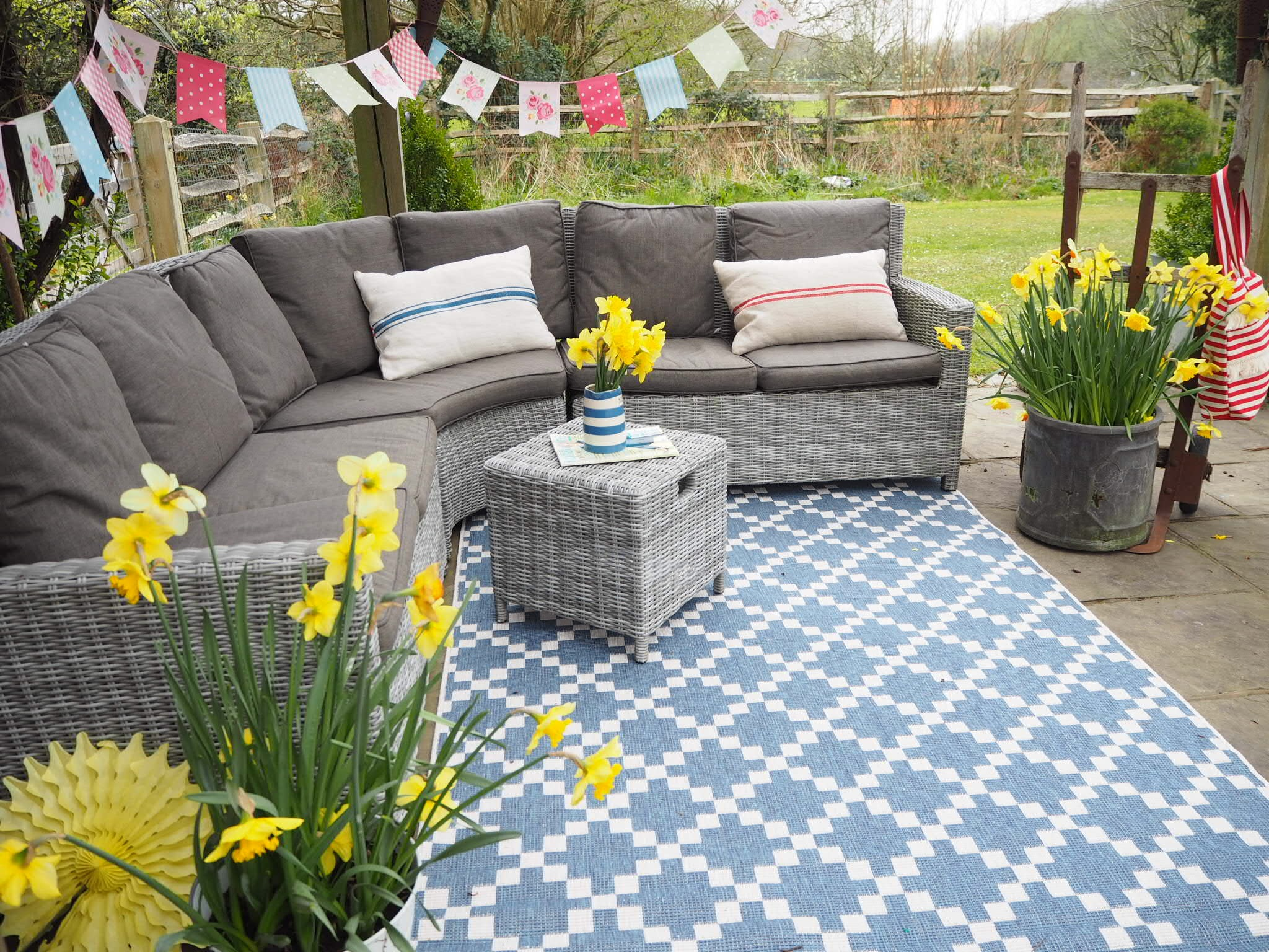 getting stuff done in heels, very network, out door rug, outdoor inspiration, garden inspo, wicker furniture, bunting,