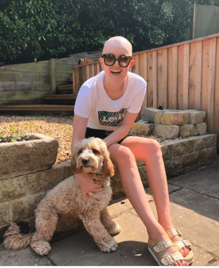 a brave young woman with no wig, sharing her experience of blood cancer, she is sitting in the garden with her dog