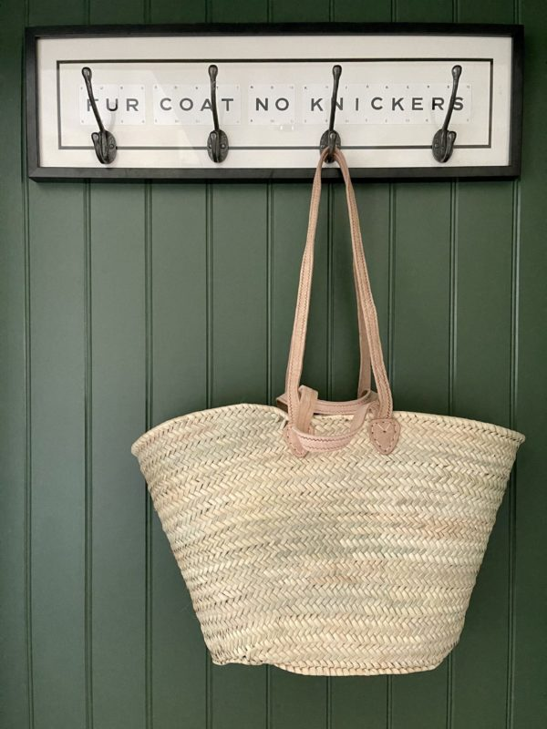 straw basket hanging on a green panelled wall