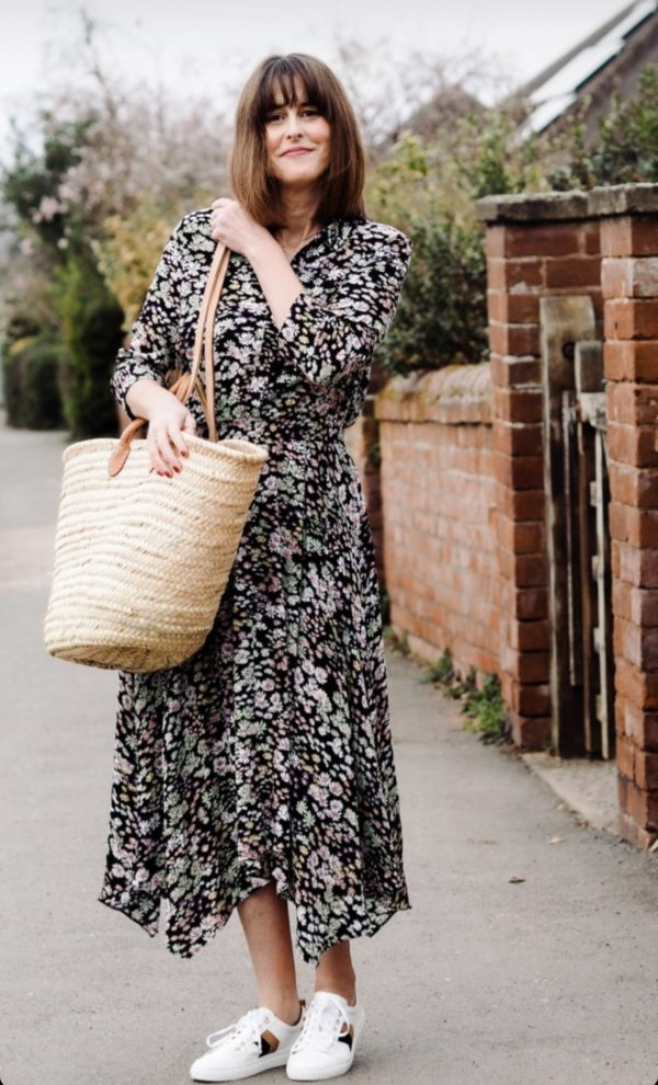 a lady wearing a spring dreed walking down a quaint lane with a large french basket for her shopping